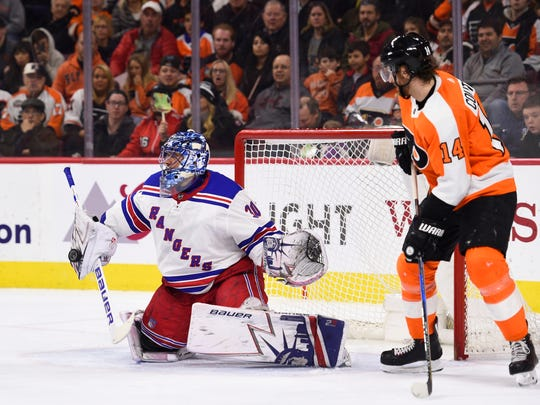 Apr 7, 2018; Philadelphia, PA, USA; New York Rangers goalie Henrik Lundqvist (30) makes a save as Philadelphia Flyers center Sean Couturier (14) look on during the second period at Wells Fargo Center.
