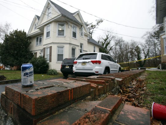 Beer cans and cups litter the yard as Newark police