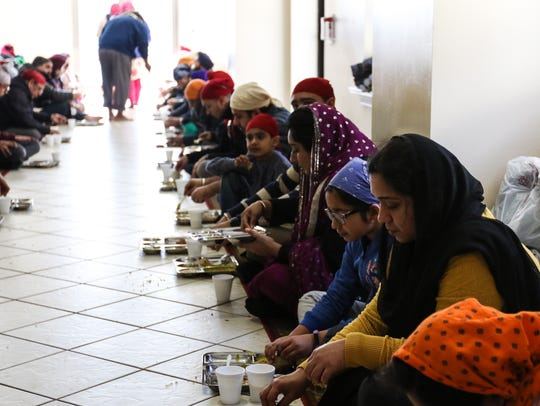 People gather to eat after service at Langar, a Sikh