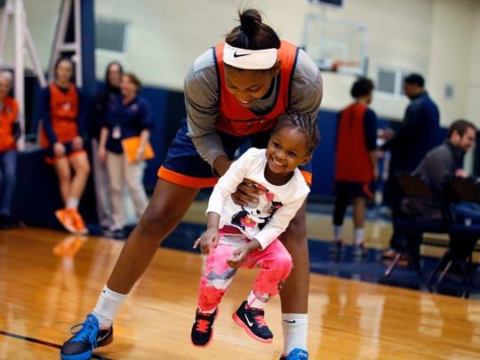 In this Jan. 27 photo, Ngoty, the adopted daughter of coach Joanne Boyle, smiles as she plays with Aliyah Huland El after a practice of the Virginia women's basketball team in Charlottesville. Boyle has developed a unique arrangement. Ngoty spends much of her day with her grandmother, then often turns up in the gym near the end of practice. She is getting to know the arena _ and her mother's office _ almost as well as her new house.