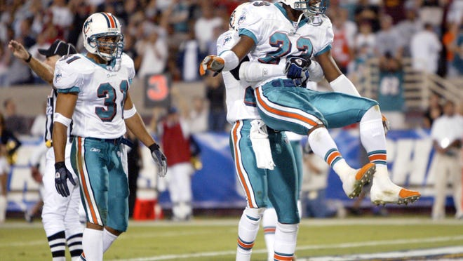Former Miami Dolphins cornerback Patrick Surtain is lifted by teammate Sam Madison after making an interception in a game agianst San Diego.