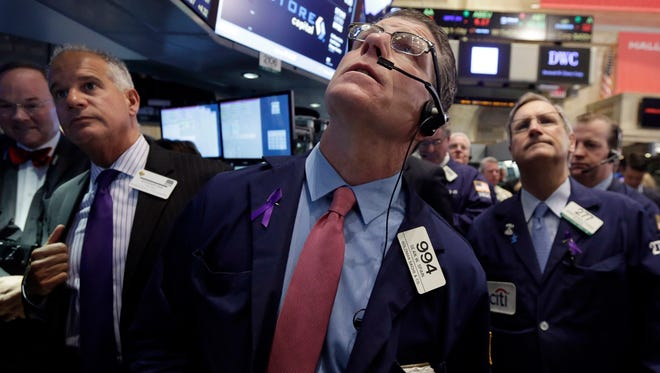 Trader Sean Spain, center, works on the floor of the New York Stock Exchange, Tuesday, Nov. 18, 2014.