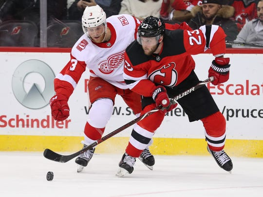 New Jersey Devils right wing Stefan Noesen (23) plays the puck while being defended by Detroit Red Wings defenseman Nick Jensen (3) during the second period at Prudential Center.