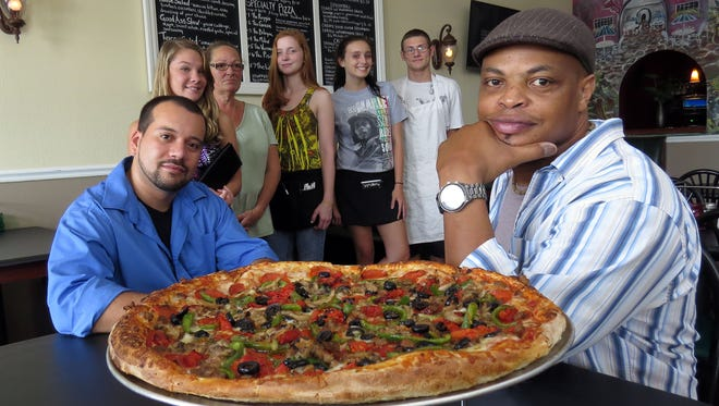 Former football standout Reggie Slack, right, with the employees of his Reggie's House of Pizza (l-r) John Claudio, general manager, Alanna Tremblay, Josie Allen, Elizabeth Williams, Tori Spenler and Trevor David.