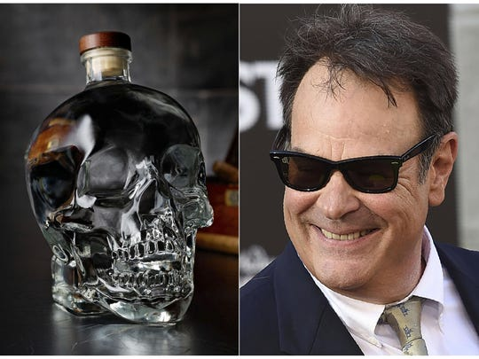 "This combination photo shows actor and businessman Dan Aykroyd at the Los Angeles premiere of ""Ghostbusters"" on July 9, 2016, right, and a bottle of his Crystal Head Vodka."