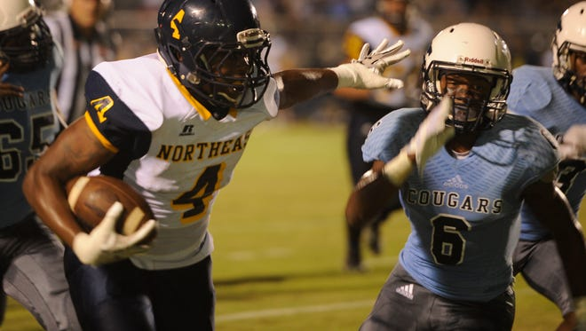 Northeast's Derecus Washington carries the ball in the first half as Centennial's Jariel Wilson defends on the play.