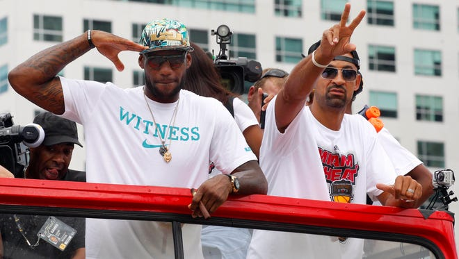 Miami Heat players LeBron James and Juwan Howard ride through downtown Miami during the 2013 Heat championship celebration parade.