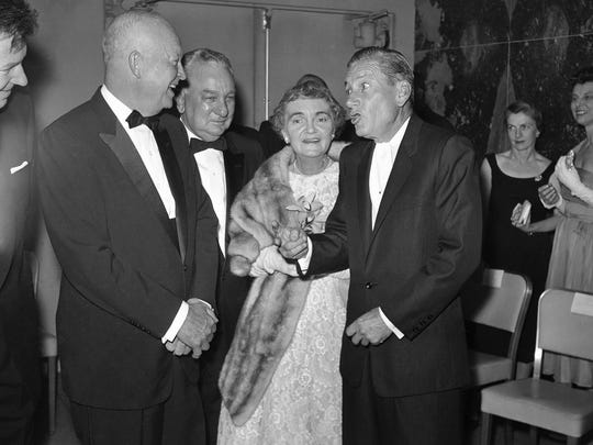 """Songwriter Hoagy Carmichael (right) gets a laugh from President Dwight Eisenhower (left) as he tells a story for Rep. Charles A. Halleck, R-Ind, and his wife, Blanche A.(White) Halleck before the March 10, 1960, dinner of the Indiana State Society honoring Halleck as """"Hoosier of the Year."""""""