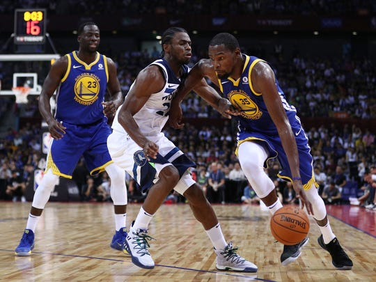 The Warriors' Kevin Durant tries to dribble around