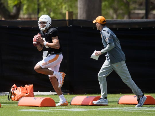 Jarrett Guarantano participates in a drill as quarterbacks coach Tyson Helton coaches during a Vols football practice at the University of Tennessee on Saturday, March 31, 2018.