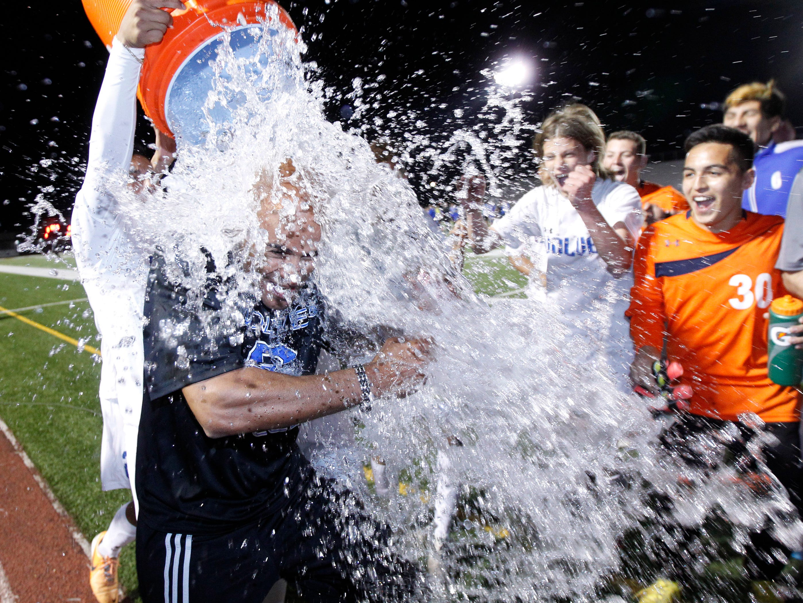 Chandler head coach Sasha Hunter gets doused after their 3-2 win against Sandra Day O'Connor in their Division I boys soccer championship Saturday, Feb. 14, 2015 in Gilbert, Ariz.