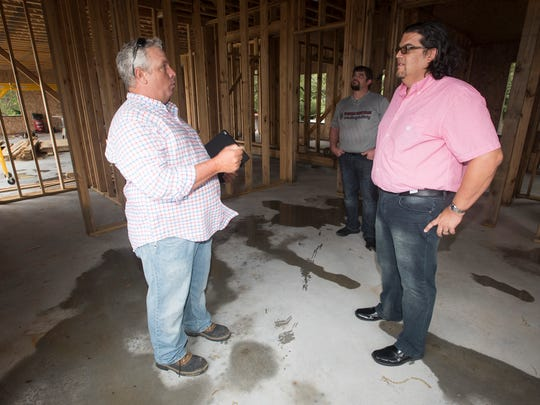 "Builder, David Butler, left, HVAC contractor, Danny Marshall, center, and Smart Home Pensacola Project Manager Dave Robau reviews plans of the state of the art technologies that are being incorporated into this new home under construction off Bayshore Drive, Thursday morning June 28, 2018. Once completed the new ""green"" home is expected to generate its own electricity without any assistance from the power grid."