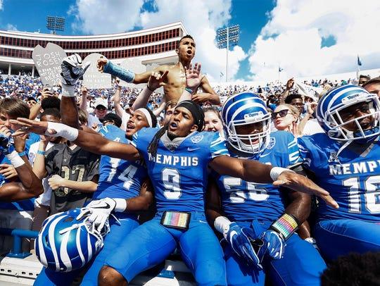University of Memphis Jamil Collins (middle) celebrate