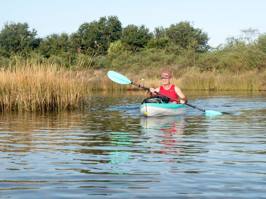 Dan Lindemann kayaks through the marsh next to Bruce Beach in Pensacola on Tuesday, November 7, 2017.  A fish hatchery is proposed to be built on the Bruce Beach property.
