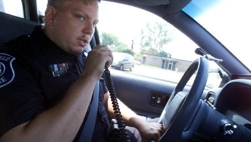 Southfield police officer Dave McCormick looks for  stolen cars, June 6, 1999.