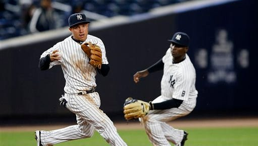 New York Yankees third baseman Ronald Torreyes (17) fields a ground ball as New York Yankees shortstop Didi Gregorius (18) backs up the play for the final out in the ninth inning of the Yankees 16-6 victory over the Houston Astros in a baseball game in New York, Wednesday, April 6, 2016.