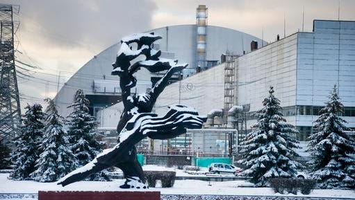 The monument to the victims of the Chernobyl tragedy is in front of a new shelter installed over the exploded reactor at the Chernobyl nuclear plant, Chernobyl, Ukraine, Tuesday, Nov. 29, 2016. A massive shelter has finally been installed over the exploded reactor at the Chernobyl nuclear plant, one of the most ambitious engineering projects in the world.