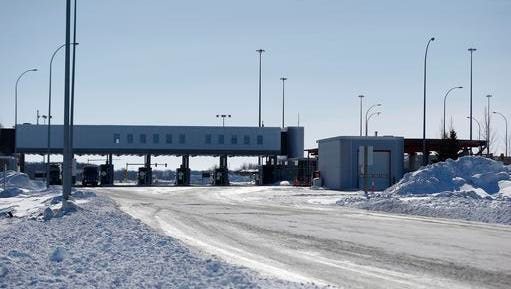 This Feb. 9, 2017, file photo shows the Canada and United States border crossing near Emerson, Manitoba.  Desperate immigrants are flowing across the U.S. border into Canada. America's neighbor to the north is increasingly being seen as a haven for asylum seekers turned away by the U.S., and are willing to chance a walk across the border in dangerous cold to get there.