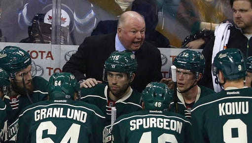 In this March 19 file photo, Minnesota Wild coach Bruce Boudreau speaks to his team during a timeout in the first period of an NHL hockey game against the Winnipeg Jets in Winnipeg, Manitoba.