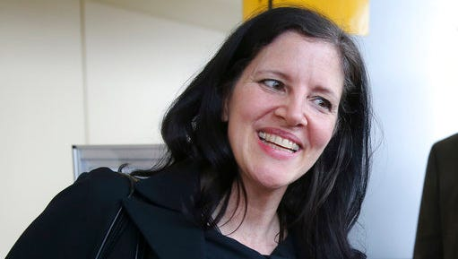 FILE - In this April 11, 2014 file photo, filmmaker Laura Poitras smiles after arriving at John F. Kennedy International Airport in New York. Poitras' travel nightmare began a decade ago when the award-winning documentary filmmaker started getting detained at airports every time she tried to step foot back in the United States. She would be stopped without explanation more than 50 times on foreign trips and dozens of times during domestic travel. Only now is Poitras beginning to unravel the mystery, which starts on a bloody day in Baghdad in 2004.