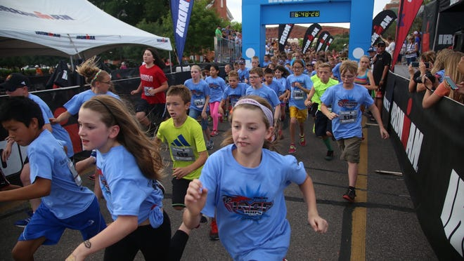 Ironkids participants take off from the starting line of the 1 mile race Friday, May 1, 2015 on Main Street in St. George