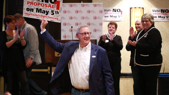 Paul Mitchell, chairman of the Coalition Against Tax Hikes and Special Interest Deals, holds up a sign signed by supporters of the Vote No on Proposal 1 campaign on Tuesday at the Troy Marriott Ballroom in Troy.