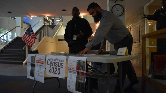 U.S. Census Bureau workers arrange 2020 Census pamphlets at a booth near the entrance to the Newburgh Free Library in October during a recruitment event.