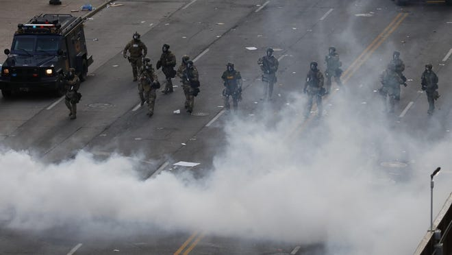 Armored vehicles, Columbus police officers and Ohio National Guard soldiers release a could of pepper gas as they drive protesters from the intersection of Broad and High Streets Sunday evening.