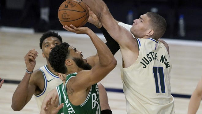 Celtics forward Jayson Tatum had some difficulty getting by the defense of Milwaukee Bucks forward Brook Lopez, right, during the game Friday night in Lake Buena Vista, Fla.