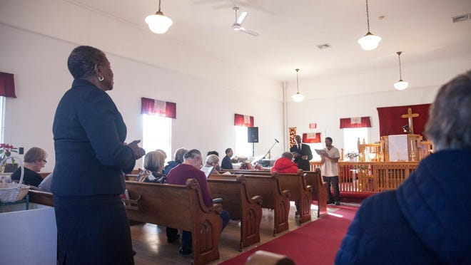 The Rev. Barbara Simmons, left, pastor of Bethel AME Church, leads a prayer at the church on Sever Street.