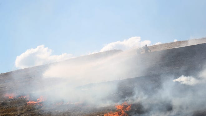 Firefighters from multiple departments battle a large brush fire at the old Thatcher Street landfill in Brockton, Monday, Aug. 3, 2020.