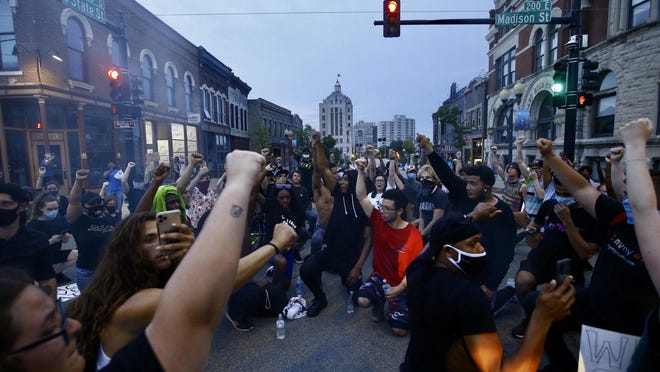 Protesters display solidarity on Tuesday, June 2, 2020, at the corner of Madison and State streets in downtown Rockford at a rally against police violence and racism.