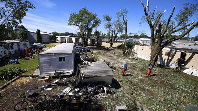 Volunteers from Little Prairie Mennonite Church in Dixon clear debris from Candlelight Mobile Home Park on Tuesday in Forreston. Five people were injured in Forreston when the severe storm struck on Monday.