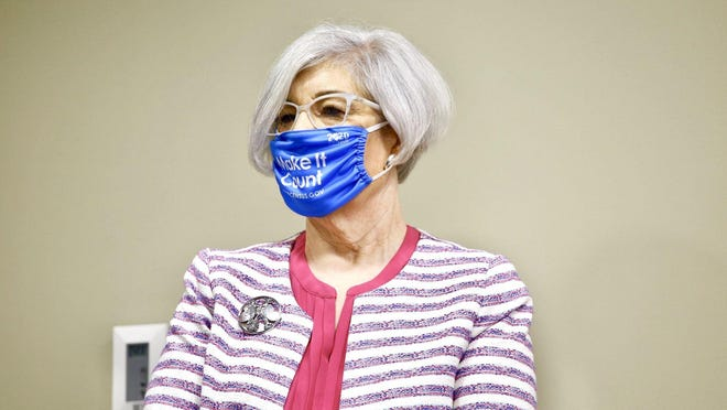 Winnebago County Health Department Administrator Sandra Martell wears a mask  Tuesday as she listens to remarks during a news conference urging safety at schools amid the coronavirus pandemic.