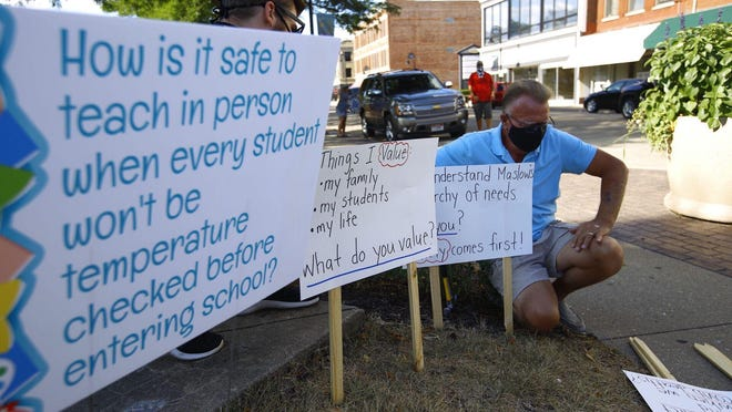 Mike Hotopp adds signs to the lawn in front of the Rockford Public Schools administration building on Tuesday, Aug. 4, 2020. Some educators and school employees want schools to resume this fall using remote instruction only.