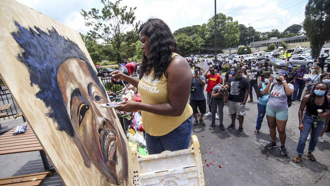 Ashley Dopson paints a picture of Rayshard Brooks in the parking lot of the Wendy's in Atlanta where Brooks, a 27-year-old black man, was shot and killed by Atlanta police Friday evening during a struggle in the Wendy's drive-thru line.