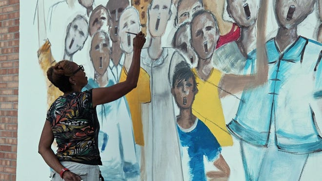 Jocelyn Woodson makes progress on her mural at the Chester I. Lewis Plaza.