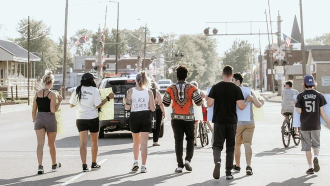 Some of the demonstrators who took part in a Black Lives Matter protest Monday in Carleton are seen with an escort from Carleton Police Department during their procession.