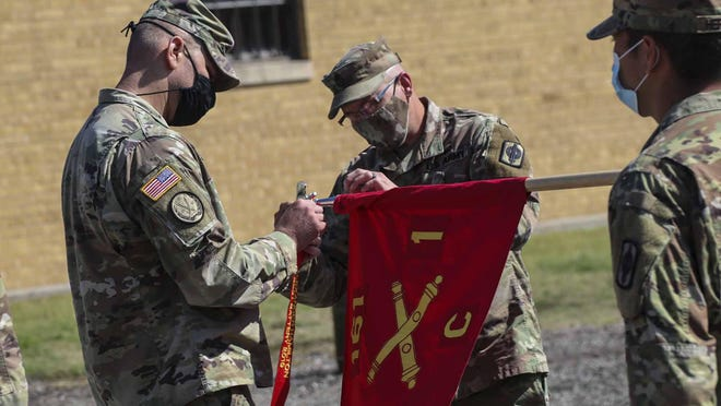 Capt. Joseph Kinsey, left, and 1st Sgt. Wesley Poell, center, the former commander and first sergeant of Battery C, 1st Battalion, 161st Field Artillery Regiment, 130th Field Artillery Brigade, attach the Hamilton Award streamer to the unit guidon at a ceremony in Newton, Sept. 12. where the unit was recognized as the best field artillery unit in the Army National Guard for 2019.