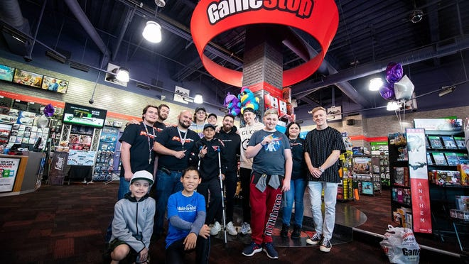 Customers and employees posing at a GameStop store.