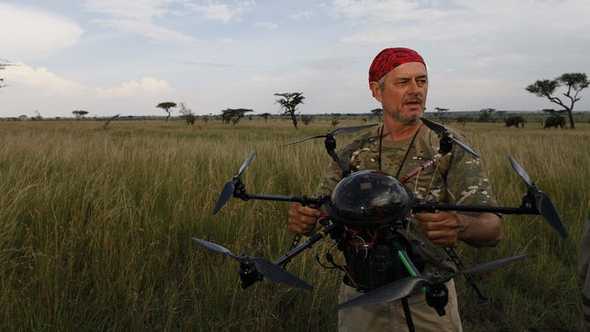 """National Geographic photographer Michael """"Nick"""" Nichols holds a mikrokopter with a camera attached to it in Serengeti National Park, Tanzania."""