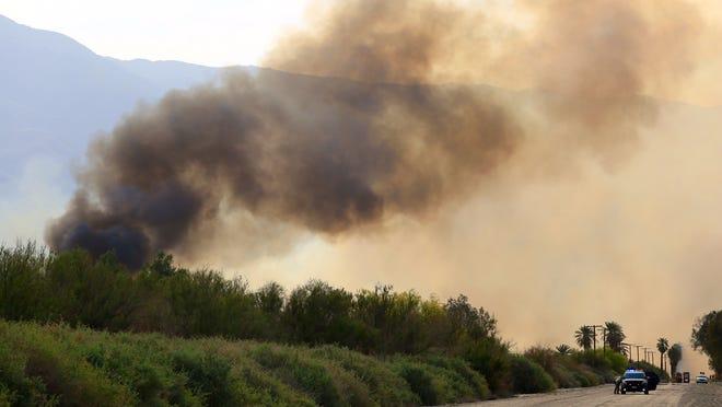 Firefighters battle a brush fire near Van Buren and Avenue 62 Friday evening.