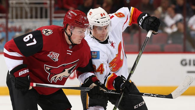 Lawson Crouse of the Arizona Coyotes and Garnet Hathaway of the Calgary Flames lock sticks off a face off on Dec. 8, 2016 in Glendale.