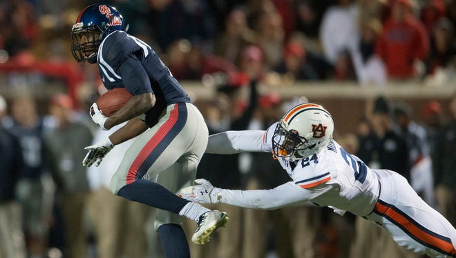 Auburn defensive back Derrick Moncrief (24) attempts to tackle Mississippi wide receiver Vince Sanders (10) during the NCAA football game at University of Mississippi in Oxford, Miss., on Saturday, Nov. 1, 2014. Auburn defeated Mississippi 35-31.