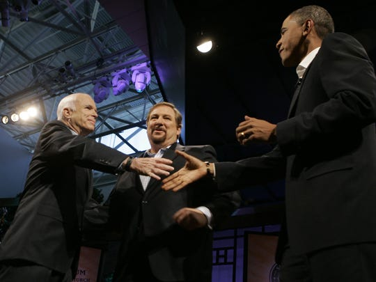 Rick Warren (center) watches as Republican presidential candidate, Sen. John McCain (left), R-Ariz., shakes hands with Democratic presidential candidate Sen. Barack Obama, D-Ill., during the Compassion Forum at Saddleback Church on Aug. 16, 2008, in Lake Forest, California.