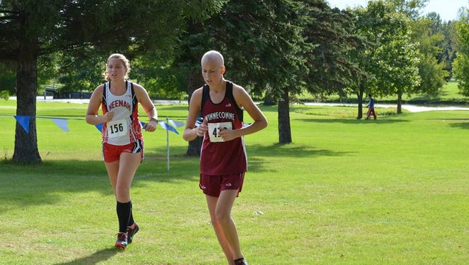 Winneconne junior Abby Johnson, right, passes another runner during the Winneconne Invitational earlier this year.