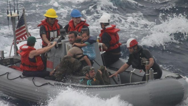 Sailors from the USS Vandegrift assist in the rescue of a family with a sick infant. Eric and Charlotte Kaufman were sailing across the Pacific Ocean with their two toddlers.