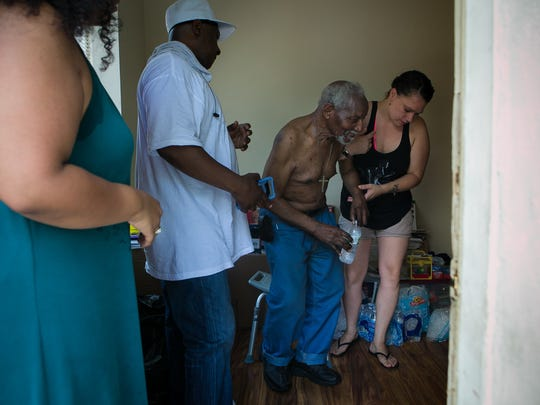 Michaelena DeJesus hands Robert King, 82, some water then helps him to a cooler room to join his wife Julia. The elderly couple had their electricity cut off for several days in the extreme heat.
