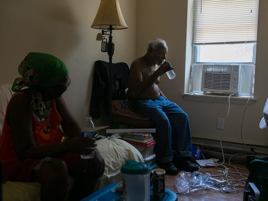 Robert King, 82, and his wife Julia, 76, try to stay cool next to an electric air conditioner that's plugged into their neighbors home as they get help from concerned area residents after the elderly couple had their electricity cut off in the extreme heat for several days.
