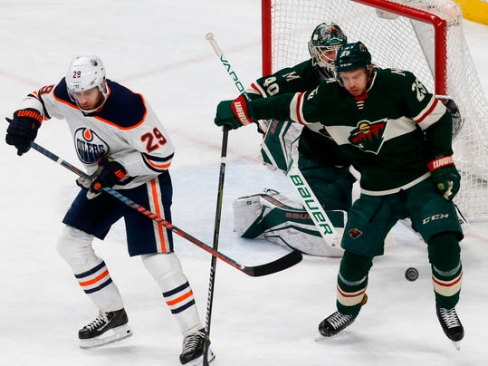 Edmonton Oilers' Leon Draisaitl of Germany, left, misses the pass as it goes behind Minnesota Wild's Jonas Brodin of Sweden as Wild goalie Devan Dubnyk guards the net in the first period of an NHL hockey game Monday, April 2, 2018, in St. Paul, Minn. (AP Photo/Jim Mone)